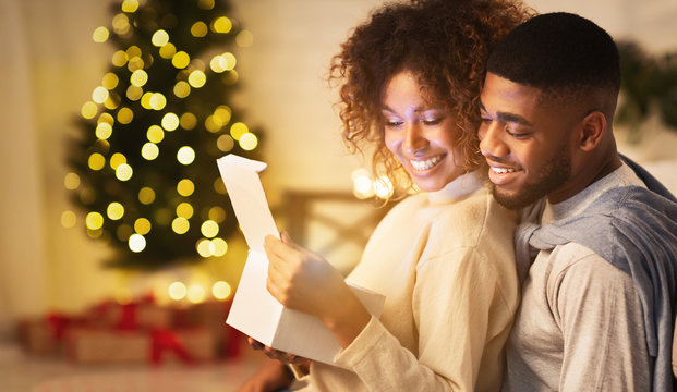 Christmas gift with love. Newlyweds opening gift box together