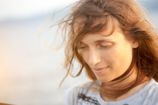 A portrait of a beautiful fair-haired young woman in windy weather near the ocean. Her hair is hanging down on her face.