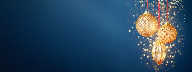 Three golden Christmas baubles hanging against the dark blue background with golden dust. New Year banner. Fotomurales