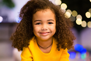 Portrait of adorable little african girl, christmas lights
