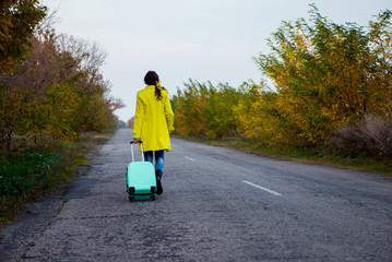 girl with a suitcase is walking along a road. The girl with wavy hair returns home. Young woman with a suitcase. Beautiful girl in a yellow raincoat in the fall. Hitchhiking on the road with luggage