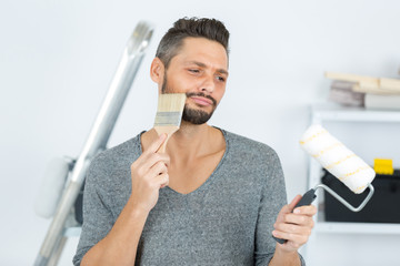 man with brush and roller ready for painting