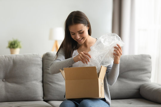 Happy young woman customer open parcel box sit on sofa