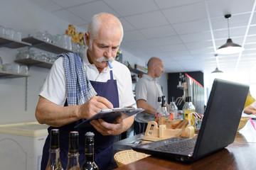 senior barman using device concept