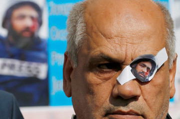 Picture of Palestinian journalist Muath Amarna, who was shot in his eye, is pasted on the eye of his colleague during a protest to show solidarity with him, in Bethlehem in the Israeli-occupied West Bank