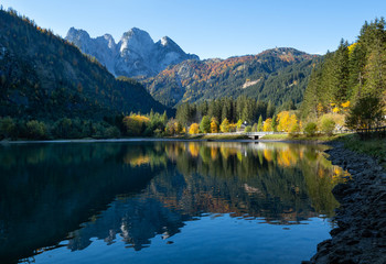 Peaceful autumn Alps mountain lake with clear transparent water and reflections. Gosauseen or Vorderer Gosausee lake, Upper Austria. Dachstein summit and glacier in far.