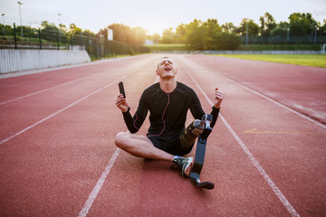 Fotomurales - Handsome caucasian handicapped young sporty man dressed in sportswear and with artificial leg sitting on racetrack, listening music over smart phone and singing.