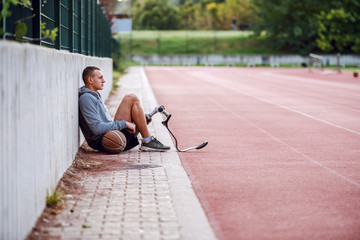 Fotomurales - Side view of handsome fit serious sportive handicapped man in sportswear and with artificial leg sitting on racetrack with basketball ball.