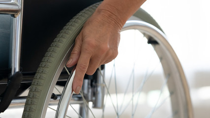 Fotomurales - Senior disabled person hand holding pushing wheel close up view