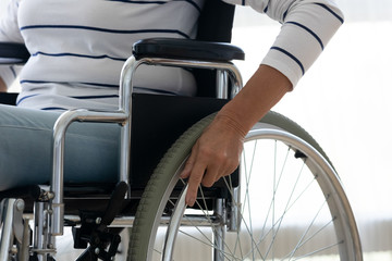 Fotomurales - Handicapped senior woman push wheel sit on wheelchair, close up