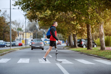 Fotomurales - Full length of handsome caucasian handicapped sportsman in sportswear, with artificial leg and backpack crossing street.