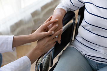 Fototapete - Nurse hold hand support handicapped senior patient on wheelchair, closeup