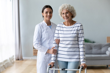 Fototapete - Female physiotherapist help old woman using walker look at camera