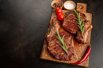 Canvas Prints two grilled beef steaks with spices on a stone background with copy space