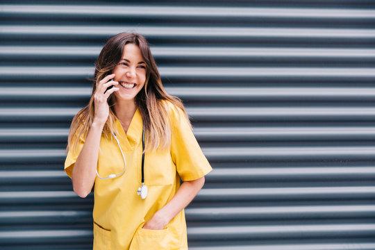 Mujer hablando por teléfono durante su descanso en el trabajo de enfermera. Feliz y sonriente con su smartphone.