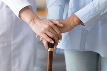 Fototapete - Female doctor holding old woman patient hand with cane stick