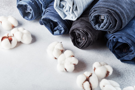 Rolled jeans and cotton flowers on light background