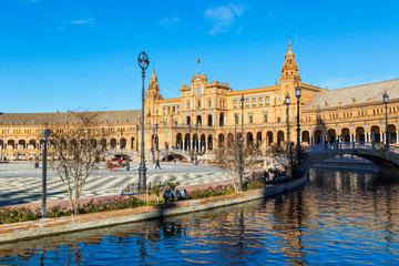 North wing of the building and river at the Spain Square (Plaza de Espana) in Seville (Sevilla) city, Andalusia, Spain. Example of Renaissance revival architecture. Bright Sunny day