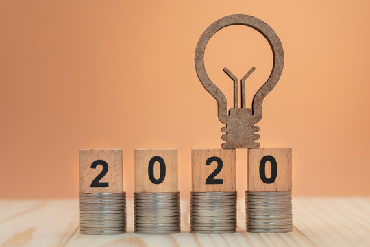 Light bulb and number 2020 made from wooden blocks on coin stacks on orange background for money, finance and business investment concept.
