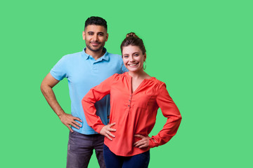 Portrait of confident attractive young couple in casual clothing standing together, holding hands on hips, smiling at camera, looking proud and happy. isolated on green background, indoor studio shot