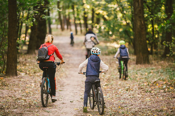 parents and kids cycling on forest trail. Young family cycling in autumn park. Family mountain biking on forest. Theme family active sports outdoor recreation. Family Cycling Through Fall Woodland