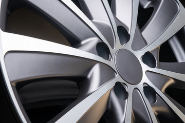 car alloy wheel close up, beautiful design of smooth curved spokes, matte gray color, on dark black background
