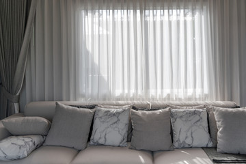 Modern set of fabric pillows marble pattern and brown on cloth sofa with light through the beige color curtains at the window interior decoration contemporary Wall mural