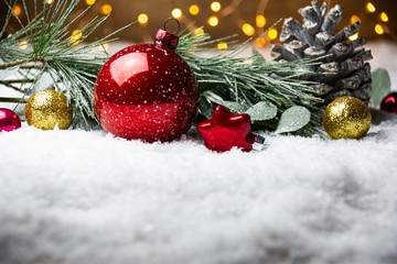 Weihnachtshintergrund mit roter Weihnachtskugel, Eukalyptus und Kiefernzweig im Schnee
