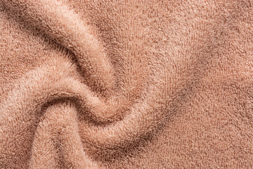 Texture of soft terry fabric in beige, swirl. Terry towel close-up.