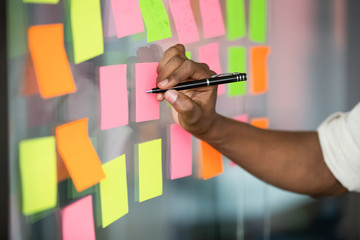 Close up african american manager writing notes on kanban board.