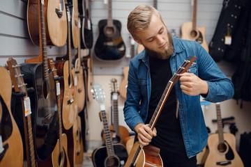 Spoed Foto op Canvas Muziekwinkel Bearded young man choosing a guitar in music store