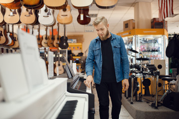 Photo sur Toile Magasin de musique Young musician poses at the piano in music store