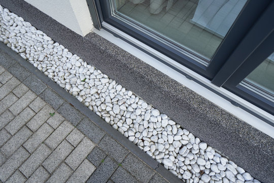 Pebbles for drainage of water along the house next to the wall. Rainwater harvesting