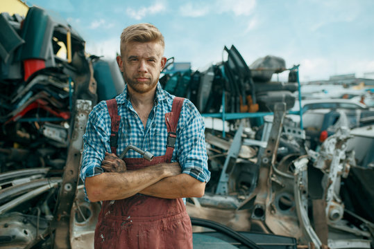Dirty male repairman on car junkyard