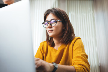 Portrait of pensive business woman wearing glasses at workplace in office. Young handsome female worker using modern laptop