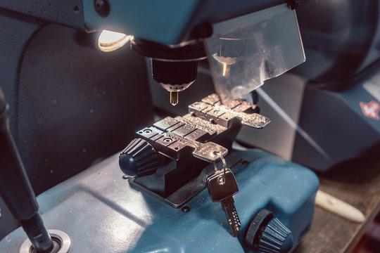 Locksmith cutting key with his machine