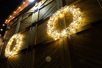 Barn house decorated with christmas lights photographed on a winter night, this wreath stands out against the weathered wooden background.