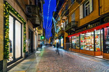 Cobblestone street and shops decorated with Christmas illumination in evening in Alba, Italy.