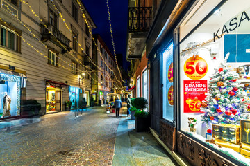 Shops on evening cobblestone street decorated with Christmas lights in evening in Alba.