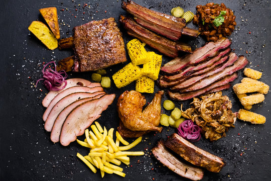 Grill restaurant menu. Top view of sliced smoked beef, pork meat, roasted poultry assortment and vegetable dishes.