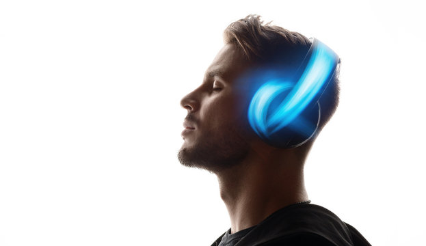 Portrait of man in headphones listening music with closed eyes. White background. Blue neon light.
