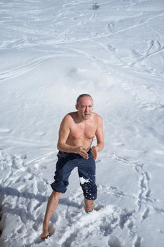adult man practicing cryotherapy, in the snow