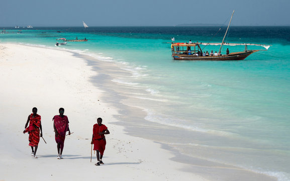Masai, entertaining tourists on the beach in Nungwi. Zanzibar, Tanzania, East Africa.