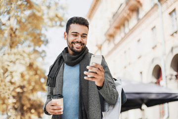 Young handsome student man using smartphone. Smiling joyful guy autumn portrait. Cheerful men wearing warm clothes holding mobile phone in a city in winter.