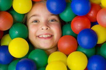 Little girl in the pool with colored balls