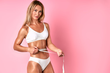Pretty cheerful woman standing against pink wall with white measure tape in hands, showing dieting results, looking confidently at camera, satisfied by measurement, dressed in white underwear
