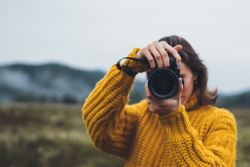 Wall Mural - photographer girl hold in hands video camera take photo on background autumn foggy mountain, tourist shooting nature mist landscape, photo lens closeup