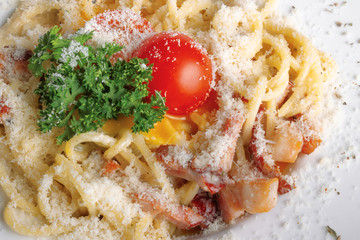 typical spaghetti alla carbonara  with raw egg and bacon. served on a white plate with grated Pecorino cheese. decorated with cherry tomato and parsley. top view close up