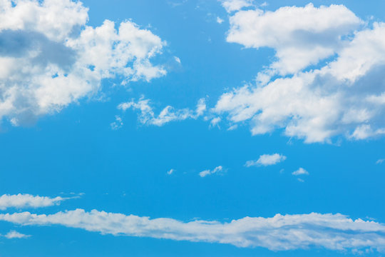 azure sky with puffy clouds. beautiful springtime nature background. dynamic side lit cloudscape
