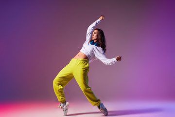 Pretty bright professional dancer performing house dance isolated on light coloured background, dancing on tiptoe, raising hands up, looking away, focused on training